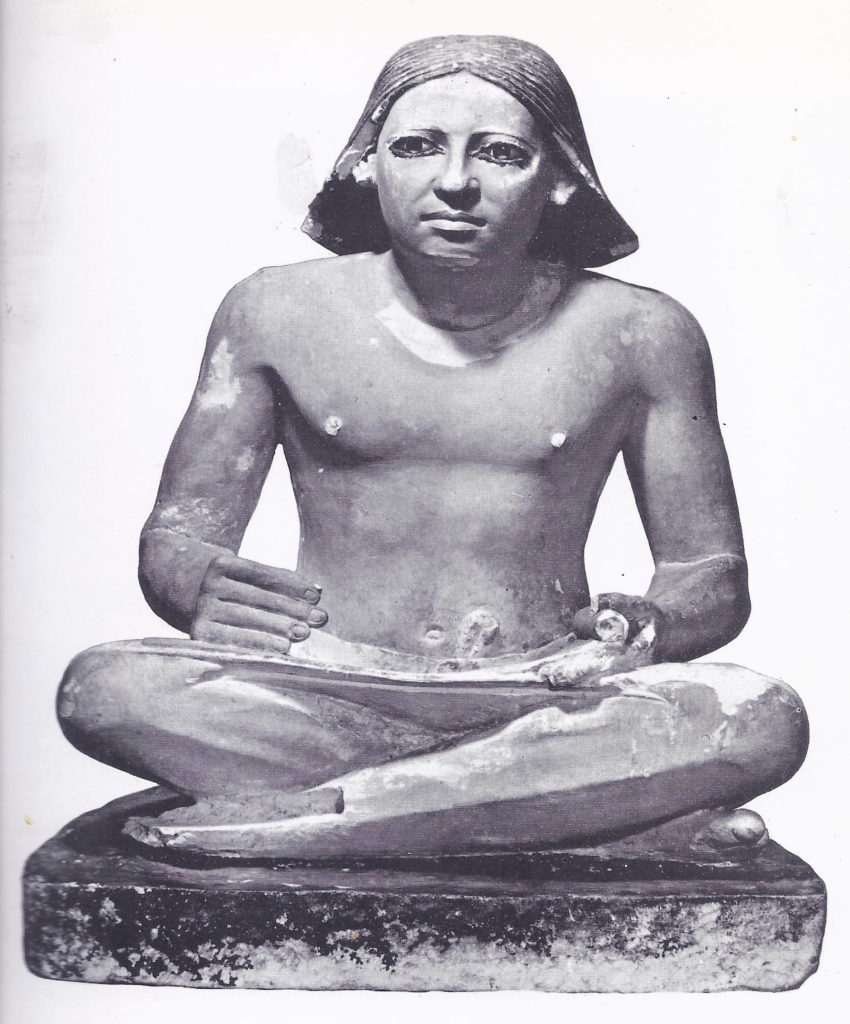 Seated figure of a scribe, showing how a roll of papyrus was held in the left hand gradually unrolled in use.